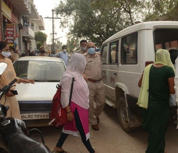 कैफे के अंदर से पकड़ी गईं महिलाओं को ले जाते हुए पुलिस।
