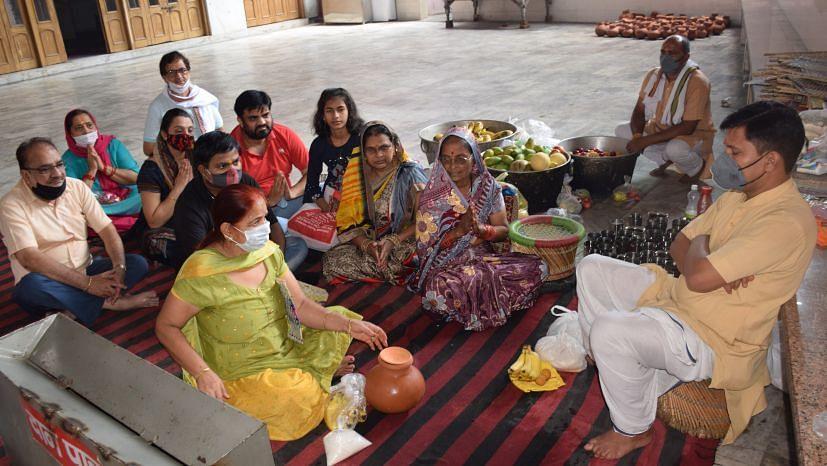 रुद्रपुर लक्ष्मी नारायण मंदिर में पुरोहित को कलश व फलों का दान करते लोग।