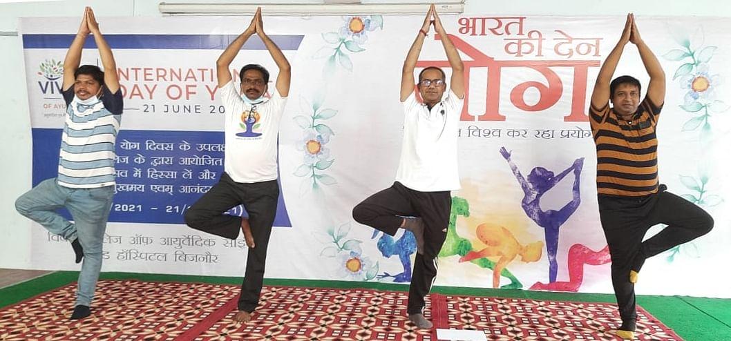 बिजनौर में विश्व योग दिवस पर विवेक कॉलेज में योग करते शिक्षक।
