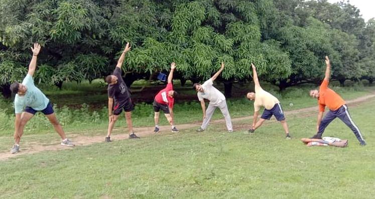 बिजनौर में विश्व योग दिवस पर जैन फार्म में योग करते गोविंदा मॉर्निंग क्लब के सदस्य।