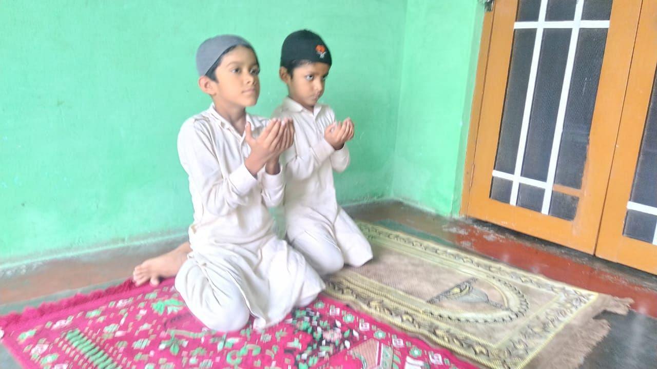 बाजपुर में एक घर के अंदर नमाज अदा करते बच्चे।