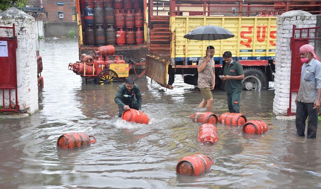 रुद्रपुर में गैस एजेंसी कार्यालय परिसर में बरसाती पानी में बहते सिलिंडर।