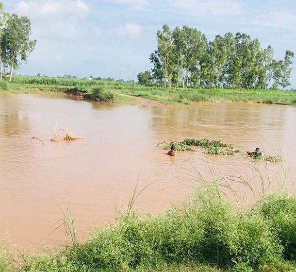 गांव सबगा स्थित मारकंडा नदी में डूबे व्यक्ति को ढूंढते तैराक।