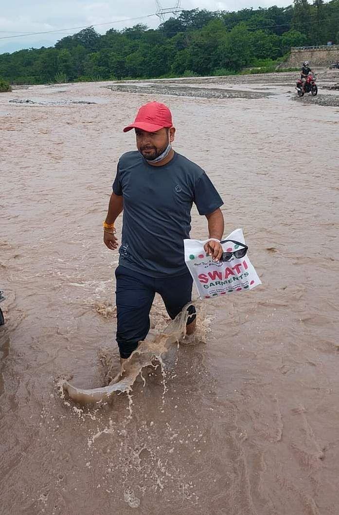 यमकेश्वर ब्लॉक के बीन नदी में मोटरपुल न बनने से जान जोखिम में डालकर नदी पार करते लोग।