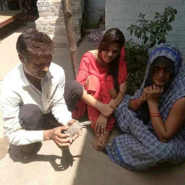 राठ के बसेला में जीवित बचे कछुए को दुलारते राजेश विश्वकर्मा व गमगीन परिवार