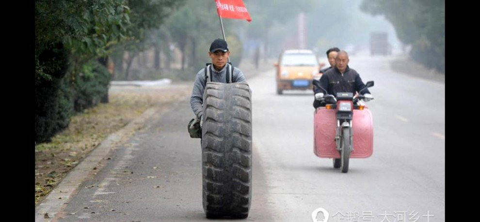 Wang Hao begun to walk from his hometown to Beijing rolling an old 135-kilogram tire