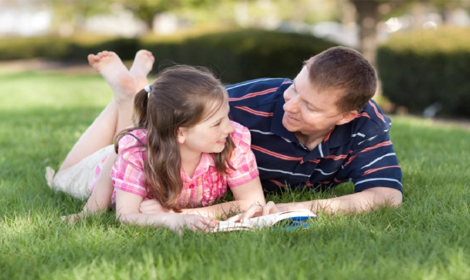 father-daughter-reading-outside
