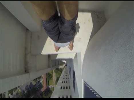 acrobat does a handstand on the edge of 24 storey building
